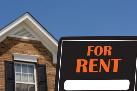 A black and orange for rent sign with a brick house in background