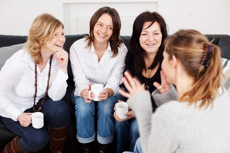 Happy female friends holding coffee cups while communicating at home