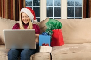 beautiful blond female sitting on a couch using a laptop to shop for Christmas gifts