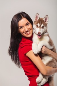 young woman with siberian husky puppy