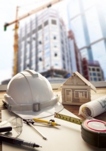 safety helmet blue print plan and construction equipment on architect and engineer working table with building construction