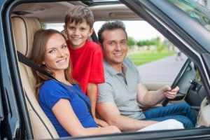 Family with one kid is travelling by car, smiling and looking at camera