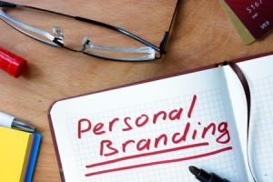 42303925 - notepad with personal branding on office wooden table.