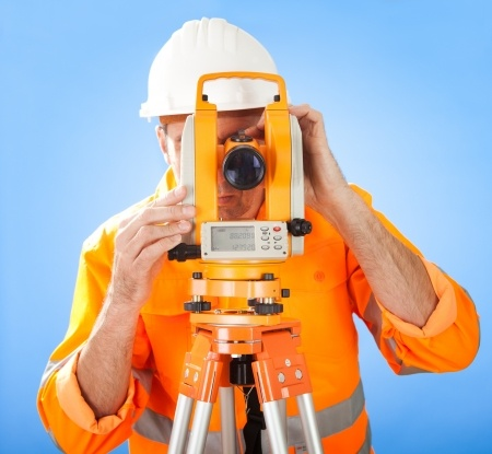 Portrait of Senior land surveyor working with theodolite at construction site