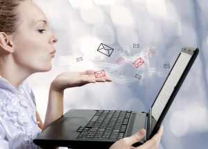 Concept - young attractive woman with laptop computer sending emails on forum, chat or blog. Blogger
