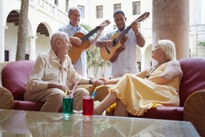 senior caucasian couple sitting in bar at hotel and listening to musicians playing guitar. Horizontal shape