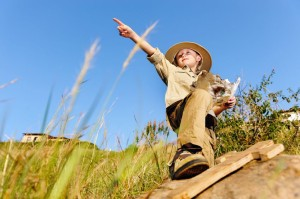 young child playing pretend adventure explorer with wooden sword and treasure map
