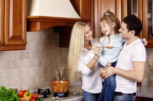 The happy young family prepares in kitchen