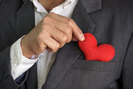 Businessman pulling out a red heart from the pocket of his suit - crm - service mind