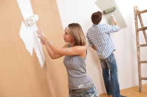 Home improvement- Young couple painting wall with paint roller