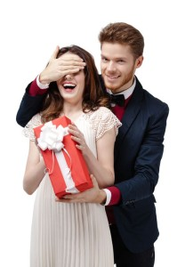 Man closes eyes of his beautiful girlfriend to give a present in red box, isolated on white