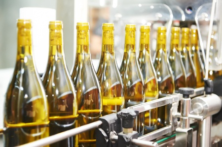 bottles with wine on bottling and sealing conveyer production line at modern winery factory
