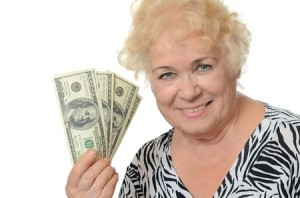 Elderly woman with dollars isolated on white