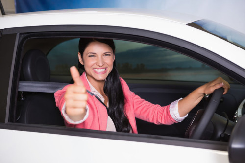 36414378 - smiling woman driving while giving thumbs up at new car showroom