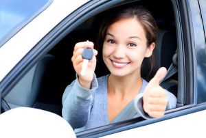 39146684 - happy girl in a car showing a key and thumb up gesture