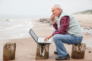 21361879 - senior businessman on beach working with notebook