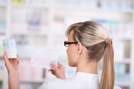 Female pharmacist picks up medicine form the shelf while confirming with the prescription