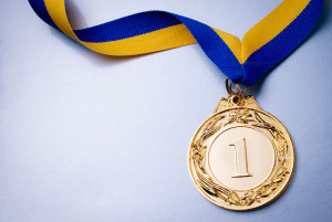 36510607 - gold medal in the foreground on yellow blue ribbon