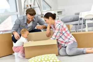 47872766 - young family unpacking boxes in new home