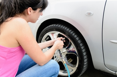 14301097 - young woman checking pressure and inflating car tires