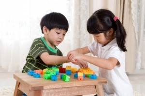24816284 - asian kids piling up building blocks