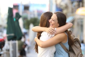 50567140 - happy meeting of two friends hugging in the street