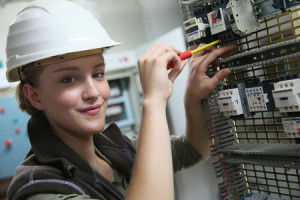 41252409 - young woman in professional training setting up electrical circuit