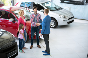 47504265 - car salesman showing new vehicle to family customers