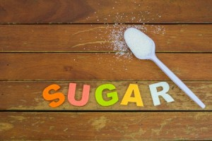 62911444 - white sugar on white plastic spoon on wooden table with word sugar