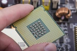 15899712 - computer microprocessor held between fingers