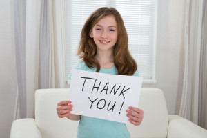 43694069 - happy girl holding board with the text thank you at home