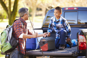 31050325 - father and son unpacking truck on camping holiday