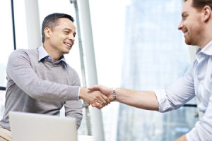 51143505 - two caucasian businesspeople smiling and shaking hands in office.