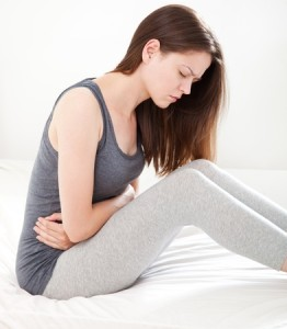 22158664 - young woman in pain sitting on bed, on white background