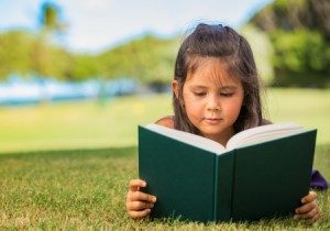 22168302 - cute little girl reading book outside on grass