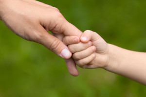 51968938 - mother holding a hand of her daughter on blurred background, closeup