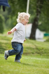 10451864 - full length of happy little boy running in garden with mouth open