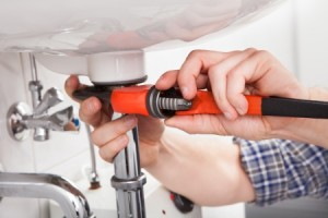 21234963 - portrait of male plumber fixing a sink in bathroom