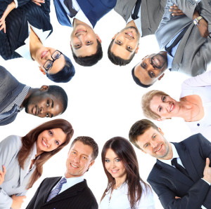 22476412 - group of business people standing in huddle, smiling, low angle view