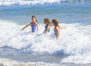 33595401 - kids playing in the ocean surf on vacation