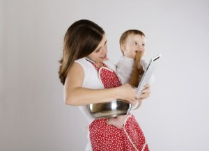 19225956 - young mother is looking at tablet with her baby