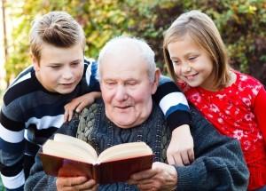 23988536 - grandpa reading a beautiful fairy tale to his grandchildren.