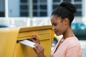 50691091 - young african woman inserting letter in mailbox