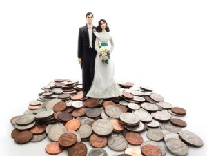27699301 - plastic wedding couple on a pile of coins - money concept