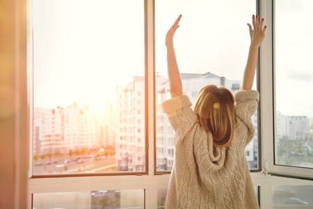 47462646 - woman near window raising hands facing the sunrise at morning