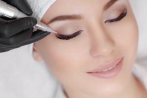 69336551 - cosmetologist making permanent make up at beauty salon