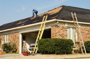 20614845 - roofer repairing the roof of a brick house in the suburbs