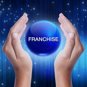 39226900 - hand showing blue crystal ball with franchise word. business concept