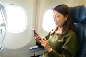 57911288 - woman use of mobile phone inside airplane
