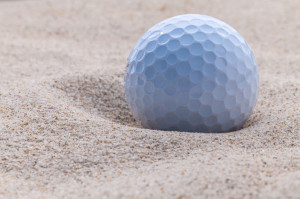 46977597 - close up golf ball in sand bunker shallow depth of field.